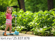Купить «Little cute girl in pink gestures with scooter in summer sunny park», фото № 25837878, снято 24 июня 2015 г. (c) Losevsky Pavel / Фотобанк Лори