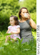 Купить «Little girl holds milk and her mother drinks milk in sunny park», фото № 25837958, снято 24 июня 2015 г. (c) Losevsky Pavel / Фотобанк Лори