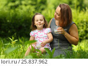 Купить «Little girl smiles and her mother with milk looks at she in sunny park», фото № 25837962, снято 24 июня 2015 г. (c) Losevsky Pavel / Фотобанк Лори