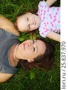 Купить «Little cute girl and her mother lie on grass and look up in park», фото № 25837970, снято 24 июня 2015 г. (c) Losevsky Pavel / Фотобанк Лори