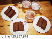Купить «Three beer mugs and three plates with toasts and garlic on wooden table», фото № 25837974, снято 23 марта 2016 г. (c) Losevsky Pavel / Фотобанк Лори