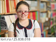 Купить «Half growth portrait of student with hair gathered in ponytail with red rim glasses, amid shelves of books, looking at camera», фото № 25838018, снято 20 марта 2015 г. (c) Losevsky Pavel / Фотобанк Лори