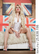 Купить «Blonde woman sits on sofa covered with fur carpet», фото № 25838198, снято 21 мая 2015 г. (c) Losevsky Pavel / Фотобанк Лори