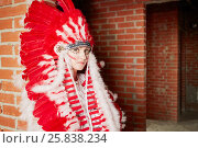 Купить «Young woman dressed in costume made of red and white feathers stands leaning her back to the brick wall», фото № 25838234, снято 13 февраля 2015 г. (c) Losevsky Pavel / Фотобанк Лори