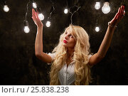 Купить «Young blonde woman stands raising her hands in dark room with many luminous lamps», фото № 25838238, снято 21 мая 2015 г. (c) Losevsky Pavel / Фотобанк Лори