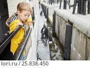 Купить «Little boy in yellow jacket on pleasure boat deck looks at boat approaching pier», фото № 25838450, снято 23 мая 2015 г. (c) Losevsky Pavel / Фотобанк Лори