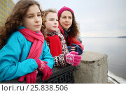 Купить «Two girls and woman look into distance on river embankment at spring day, focus on girl in middle», фото № 25838506, снято 5 апреля 2016 г. (c) Losevsky Pavel / Фотобанк Лори