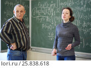 Купить «Two teachers stand near blackboard with formulas in classroom, woman speaks», фото № 25838618, снято 7 апреля 2016 г. (c) Losevsky Pavel / Фотобанк Лори