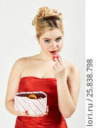Woman in red dress holds open box in shape of heart and going to bite off cookie. Стоковое фото, фотограф Losevsky Pavel / Фотобанк Лори