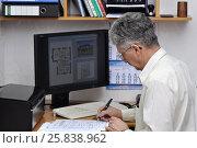 Купить «Инженер-архитектор у компьютера, за рабочим столом ставит подпись под документом», фото № 25838962, снято 25 марта 2017 г. (c) Сергей Галинский / Фотобанк Лори