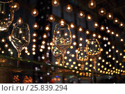 Купить «Wine glasses on a glass table illuminated lots of luminous lamps», фото № 25839294, снято 14 февраля 2015 г. (c) Losevsky Pavel / Фотобанк Лори