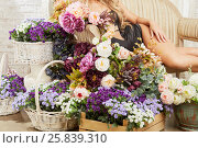 Купить «Young woman reclines on couch surrounded by mass of flowers.», фото № 25839310, снято 29 марта 2015 г. (c) Losevsky Pavel / Фотобанк Лори