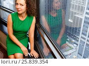 Woman sit on a sill against the background of the city through a window (2014 год). Стоковое фото, фотограф Losevsky Pavel / Фотобанк Лори