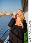 Young woman in black stands with cocktail and laughs on ship deck during sailing in city. Стоковое фото, фотограф Losevsky Pavel / Фотобанк Лори