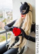 Купить «Pretty blonde woman with black cats ears holds red heart and sits on balcony», фото № 25839458, снято 15 октября 2015 г. (c) Losevsky Pavel / Фотобанк Лори