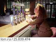 Купить «Young curly woman sits at bar counter in evening cafe», фото № 25839474, снято 28 декабря 2014 г. (c) Losevsky Pavel / Фотобанк Лори