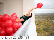 Купить «Happy woman in green dress holds many red balloons and throws away one on balcony», фото № 25839498, снято 15 октября 2015 г. (c) Losevsky Pavel / Фотобанк Лори