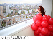 Купить «Young woman holds red balloons and poses at balcony in autumn day», фото № 25839514, снято 15 октября 2015 г. (c) Losevsky Pavel / Фотобанк Лори