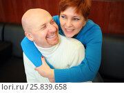 Купить «Portrait of laughing bald man and a red-haired woman sitting on a black sofa», фото № 25839658, снято 21 февраля 2015 г. (c) Losevsky Pavel / Фотобанк Лори