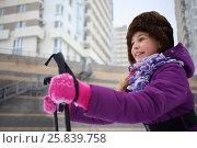 Купить «Portrait of a happy young girl in a winter hat with ski poles near the blocks of flats», фото № 25839758, снято 5 января 2015 г. (c) Losevsky Pavel / Фотобанк Лори