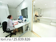 Купить «Doctor in control room, and magnetic resonance imaging machine with patient», фото № 25839826, снято 31 августа 2015 г. (c) Losevsky Pavel / Фотобанк Лори