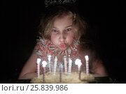 Купить «Girl with crown on head sits in dark room blowing out burning candles at birthday cake», фото № 25839986, снято 7 января 2015 г. (c) Losevsky Pavel / Фотобанк Лори