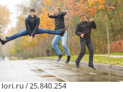 Купить «Three young men in black jackets jumping for merry-making in alley in park», фото № 25840254, снято 25 октября 2015 г. (c) Losevsky Pavel / Фотобанк Лори