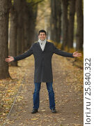 Купить «Portrait in full growth young man in gray coat with outstretched hands on alley in autumn park», фото № 25840322, снято 25 октября 2015 г. (c) Losevsky Pavel / Фотобанк Лори