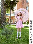 Купить «Little girl in pink dress sunhat stands on grassy lawn holding umbrella», фото № 25840370, снято 1 июня 2015 г. (c) Losevsky Pavel / Фотобанк Лори
