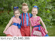 Купить «Boy in red trousers and blue shirt stands embracing two girls at grassy lawn», фото № 25840386, снято 29 мая 2016 г. (c) Losevsky Pavel / Фотобанк Лори