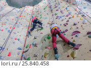 Купить «Rock climbing. Two young girls with equipment rises on specially-equipped wall for climbers», фото № 25840458, снято 25 октября 2015 г. (c) Losevsky Pavel / Фотобанк Лори