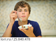Купить «Happy boy teen eats confection from saucer in kitchen, shallow dof», фото № 25840478, снято 2 сентября 2015 г. (c) Losevsky Pavel / Фотобанк Лори