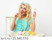 Beautiful girl with white hair licks lollipop at atble with at marshmallows. Стоковое фото, фотограф Losevsky Pavel / Фотобанк Лори