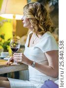 Купить «Curly woman in white drinks red wine in cozy restaurant at evening», фото № 25840538, снято 12 июля 2015 г. (c) Losevsky Pavel / Фотобанк Лори