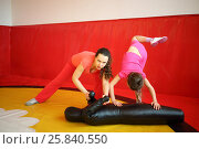 Купить «Woman and girl do fighting exercises with leather mannequin in gym with red wall», фото № 25840550, снято 20 апреля 2015 г. (c) Losevsky Pavel / Фотобанк Лори