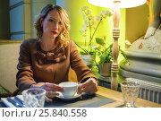 Купить «Middleaged pretty woman sits with tea and looks at camera in cozy restaurant», фото № 25840558, снято 12 июля 2015 г. (c) Losevsky Pavel / Фотобанк Лори