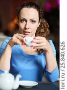 Купить «Pretty curly woman in blue dress drinks tea in cozy restaurant, shallow dof», фото № 25840626, снято 12 июля 2015 г. (c) Losevsky Pavel / Фотобанк Лори