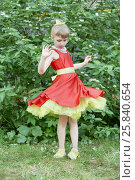 Купить «Little girl dressed in red gown with yellow underskirt spins standing outdoor», фото № 25840654, снято 29 мая 2016 г. (c) Losevsky Pavel / Фотобанк Лори