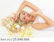 Купить «Smiling woman lies among sweets and licks lollipop on floor in studio», фото № 25840666, снято 3 сентября 2015 г. (c) Losevsky Pavel / Фотобанк Лори