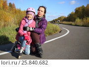 Купить «Mother with her daughter in a protective helmet on roller skates in the autumn park», фото № 25840682, снято 4 октября 2014 г. (c) Losevsky Pavel / Фотобанк Лори