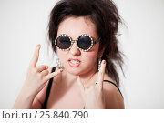 Купить «Smiling dark-haired girl model in stylish round dark glasses shows goat both hands», фото № 25840790, снято 11 января 2015 г. (c) Losevsky Pavel / Фотобанк Лори