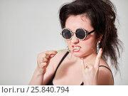 Купить «Dark-haired girl model in stylish round dark glasses shows goat and pulls chewing gum», фото № 25840794, снято 11 января 2015 г. (c) Losevsky Pavel / Фотобанк Лори