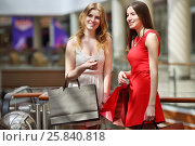 Купить «Two pretty girls with bags stand and smile in big modern store», фото № 25840818, снято 21 апреля 2015 г. (c) Losevsky Pavel / Фотобанк Лори