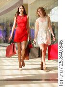 Купить «Two happy beautiful girls go with bags in large shopping center», фото № 25840846, снято 21 апреля 2015 г. (c) Losevsky Pavel / Фотобанк Лори