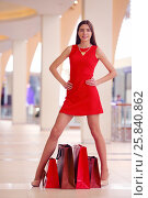 Купить «Beautiful girl in short red dress stands with bags in shopping center», фото № 25840862, снято 21 апреля 2015 г. (c) Losevsky Pavel / Фотобанк Лори