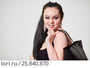 Купить «Dark-haired girl model with black bag poses at studio», фото № 25840870, снято 11 января 2015 г. (c) Losevsky Pavel / Фотобанк Лори