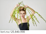 Купить «Young smiling woman in black dress holds bunches of live stems with flower buds», фото № 25840998, снято 11 января 2015 г. (c) Losevsky Pavel / Фотобанк Лори