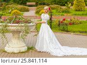 Купить «Full portrait of beautiful woman in white long dress in summer park, posing with flower pots», фото № 25841114, снято 16 июля 2015 г. (c) Losevsky Pavel / Фотобанк Лори