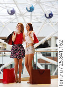 Купить «Two pretty young women with purchases stand and smile in modern mall», фото № 25841162, снято 21 апреля 2015 г. (c) Losevsky Pavel / Фотобанк Лори