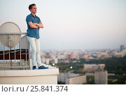 Купить «Young man in denim clothes stands crossing arms on chest on the roof leaning his back to the railing», фото № 25841374, снято 4 июня 2015 г. (c) Losevsky Pavel / Фотобанк Лори